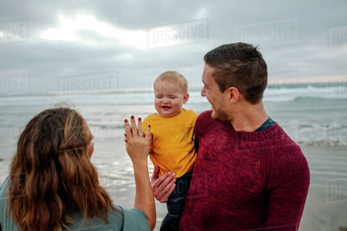 Happy baby held by father plays pat-a-cake with mom at the ocean Royalty-free stock photo