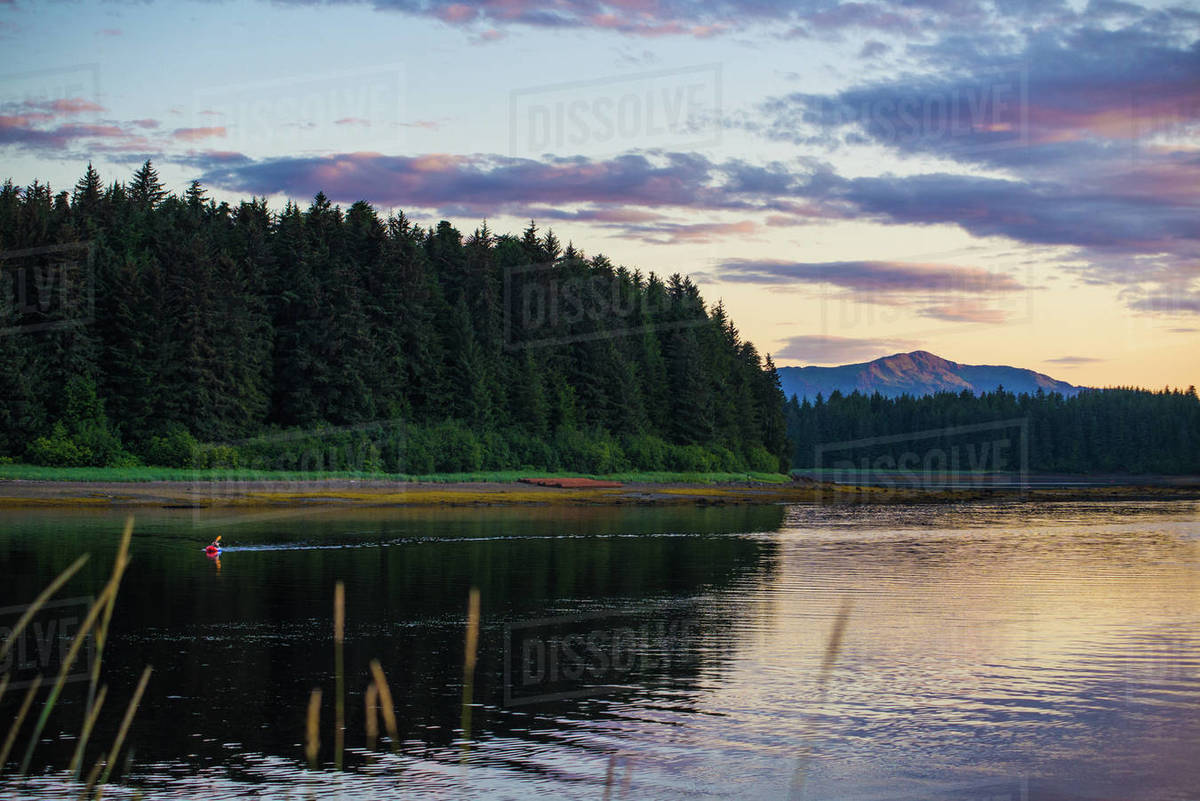 Person in a packraft paddles through an inlet during sunset in Alaska Royalty-free stock photo