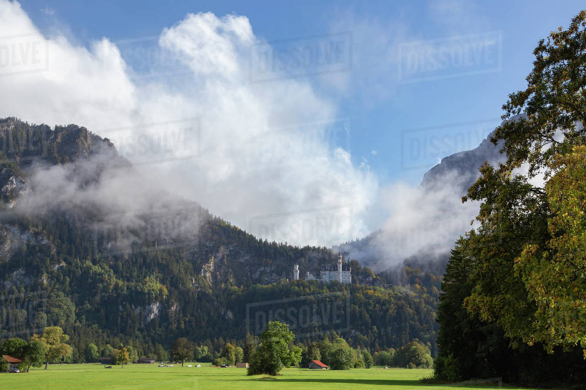 Castle Neuschwanstein sits among the clouds on a sunny autumn day Royalty-free stock photo
