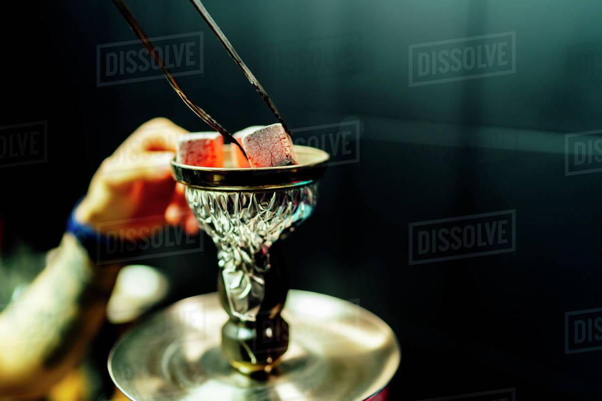 Waiter placing smoking charcoal stones for shisha Royalty-free stock photo