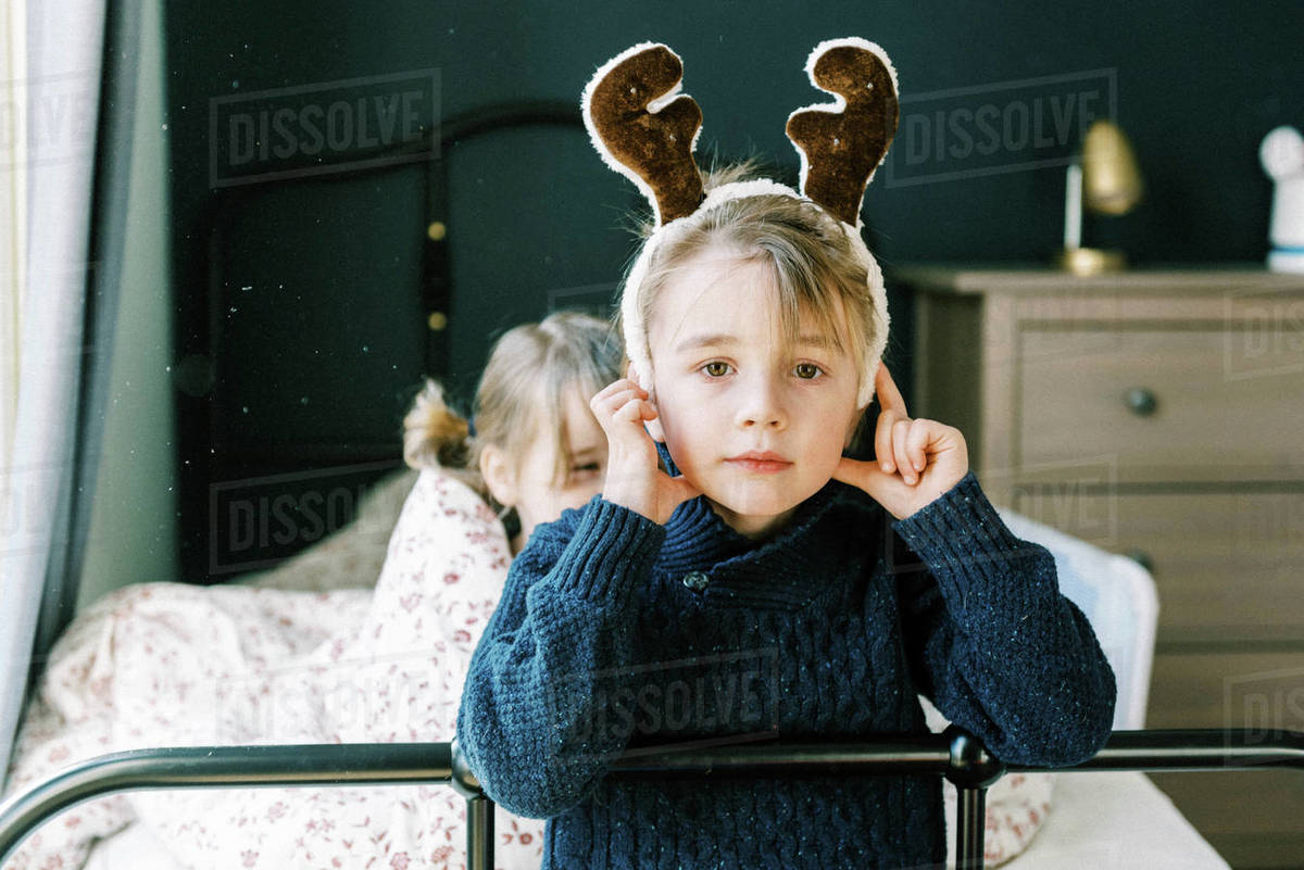 Little boy in a blue knit sweater with a reindeer hat in room on bed Royalty-free stock photo