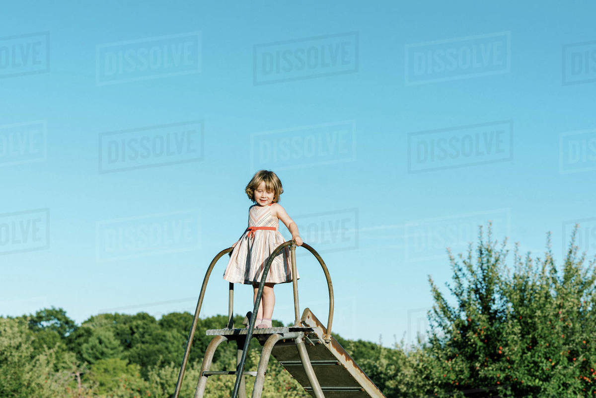 Little girl standing on top of a slide and feeling tall and brave Royalty-free stock photo