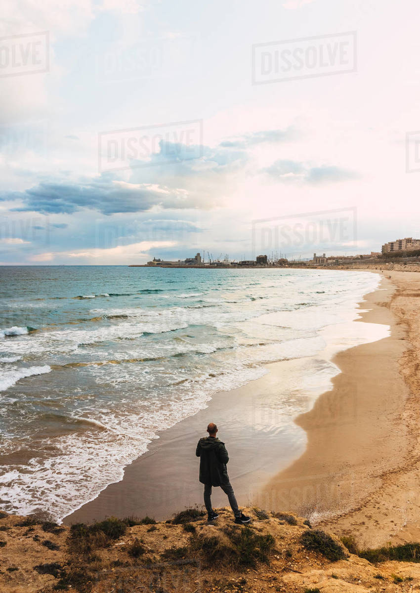 Views Of A Man From Behind Looking At A Beach In A Cloudy Sky Royalty-free stock photo