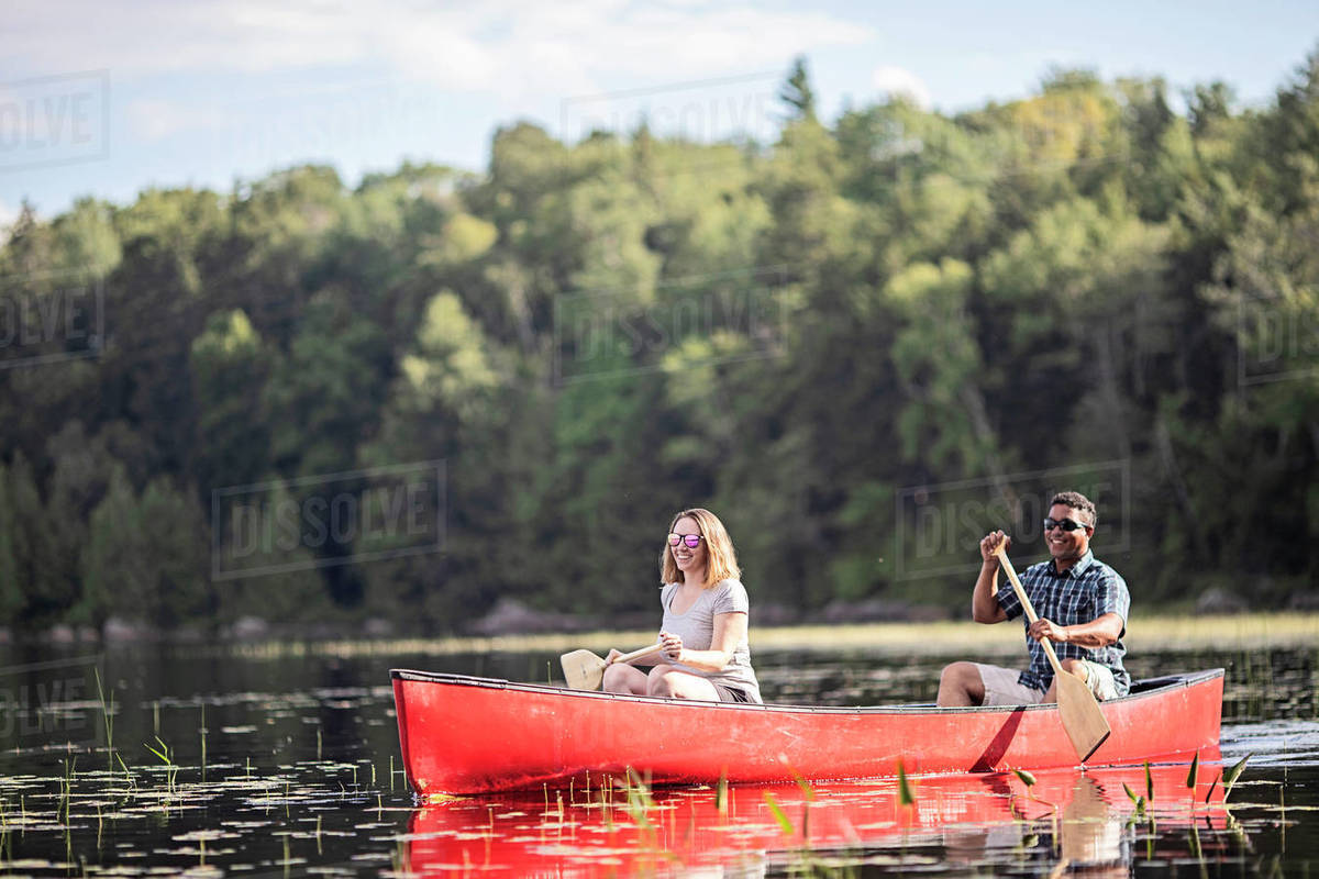 Multi racial couple paddle a red canoe on Bald Mountain Pond, Maine Royalty-free stock photo