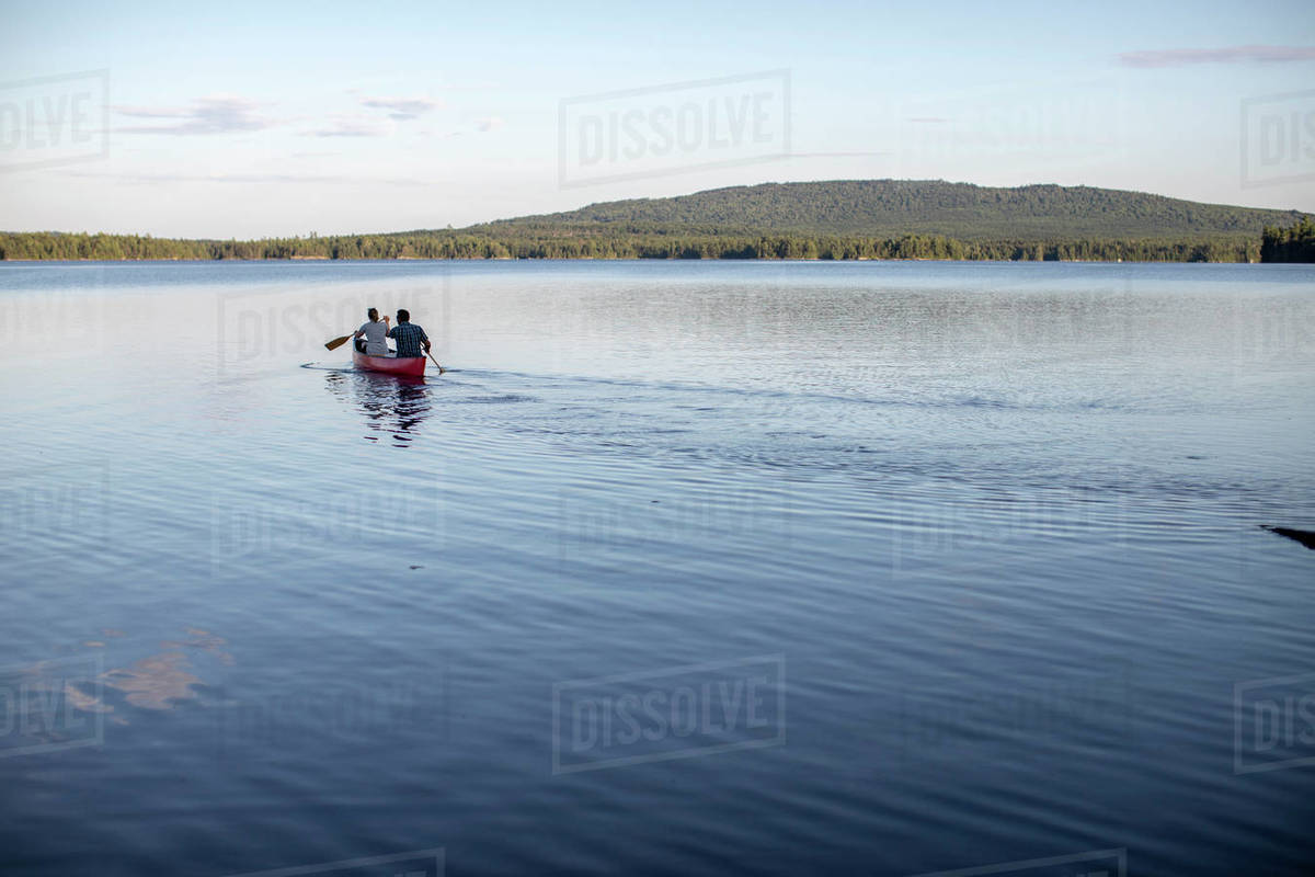 Canoe paddled by two people heads into the distance on lake in Maine Royalty-free stock photo