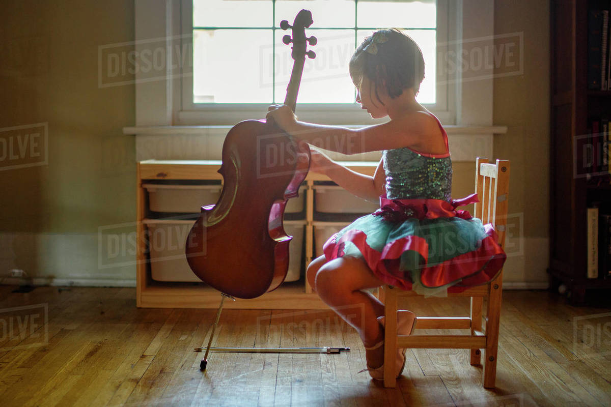 A little girl in a tutu sits in small chair by window holding a cello Royalty-free stock photo