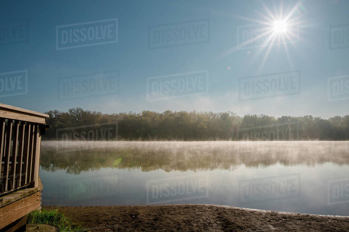 Sun rising over a foggy lake with reflected trees in early morning Royalty-free stock photo