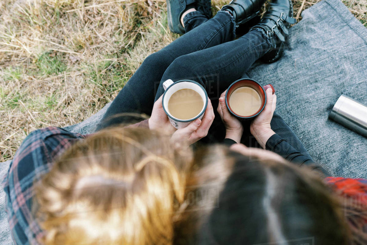 Cute lesbian couple sitting on blanket after hike drinking coffee from thermos Royalty-free stock photo