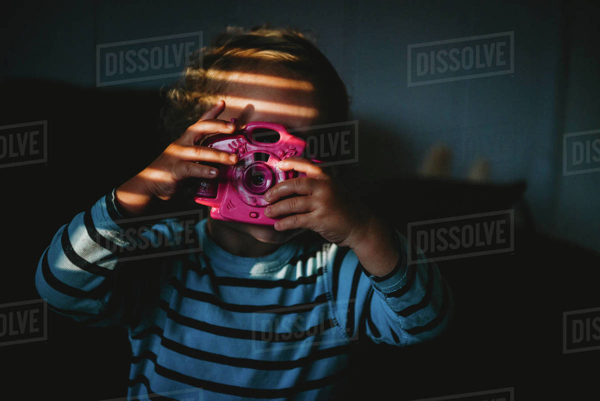 Young child pretending to take a photo with toy camera inside at home Royalty-free stock photo