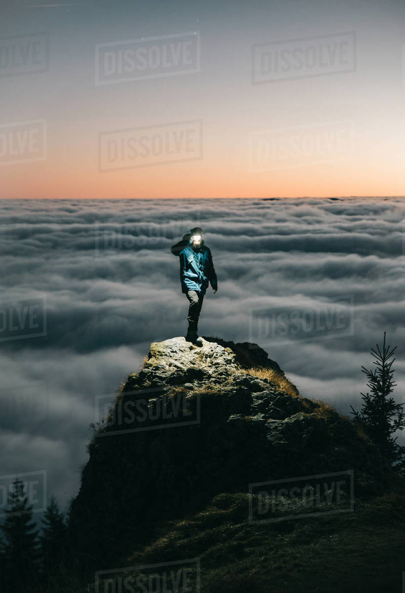 Person Standing on the Mountain Above the Clouds with Flashlight Royalty-free stock photo