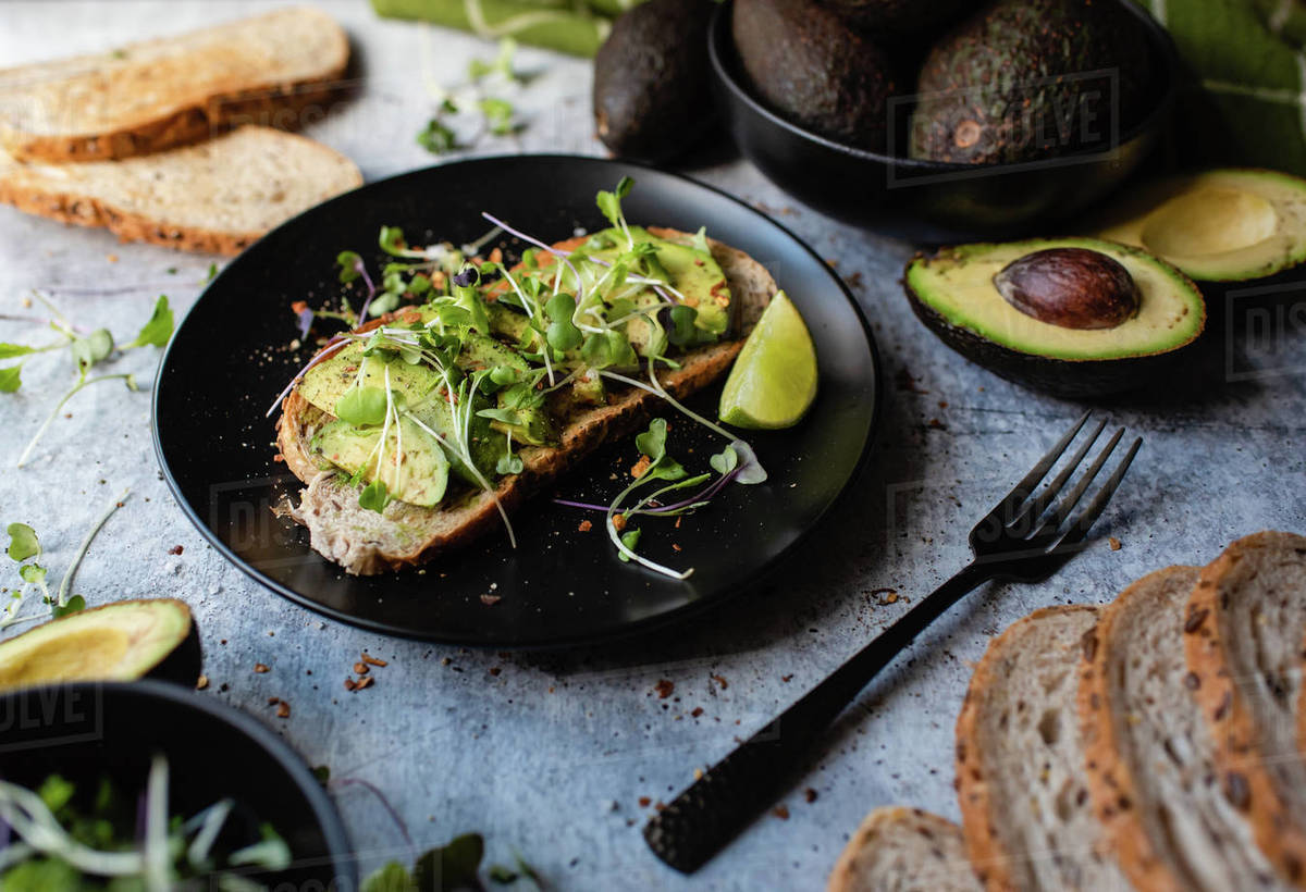 Avocado toast on a plate with ingredients around it on stone counter. Royalty-free stock photo