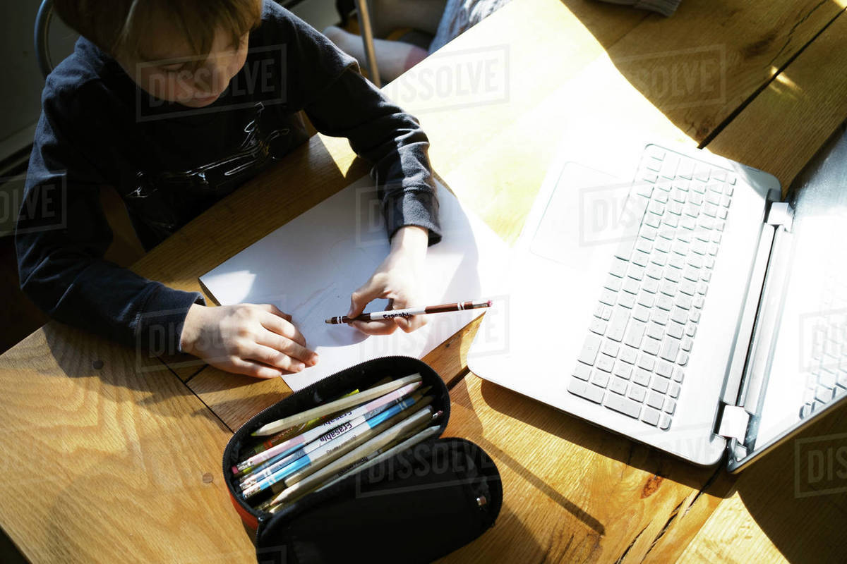 Kids in morning light sitting at table doing remote school Royalty-free stock photo