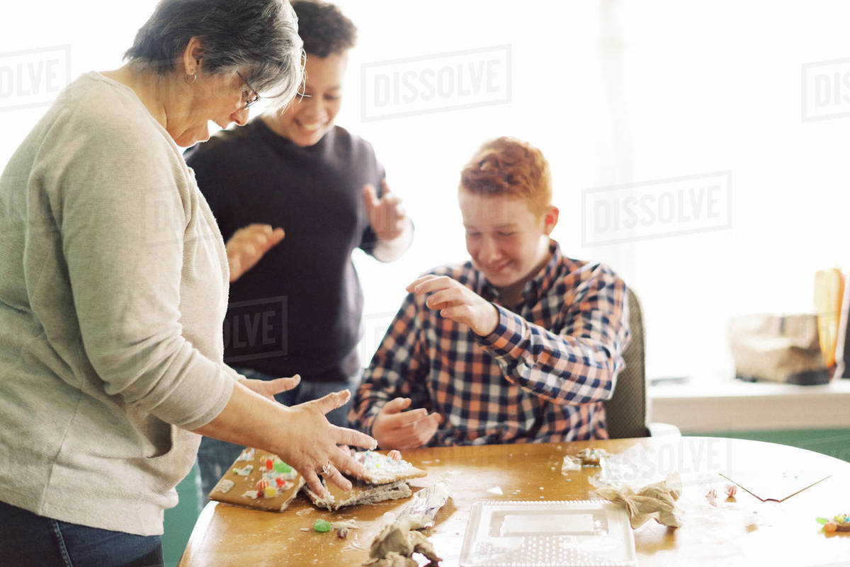 A mother and her children making a gingerbread house at dining table Royalty-free stock photo