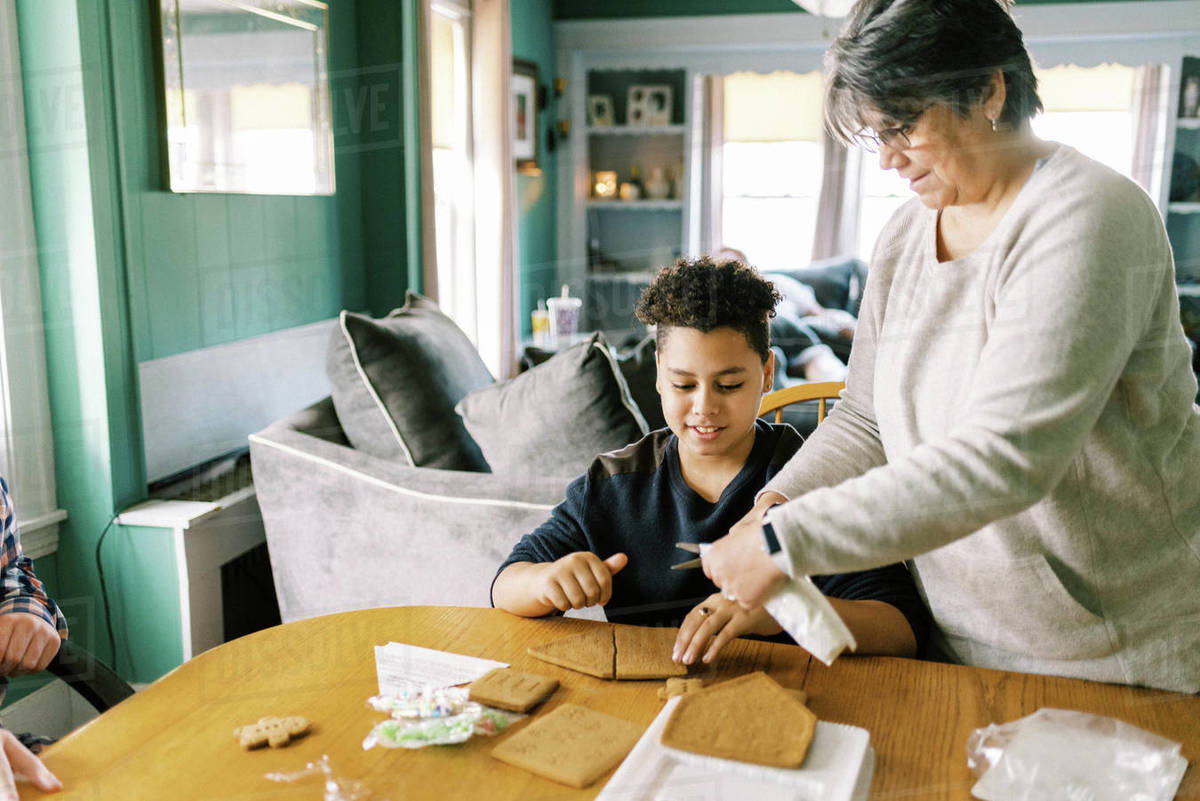 A mother and her kids making a gingerbread house for christmas Royalty-free stock photo