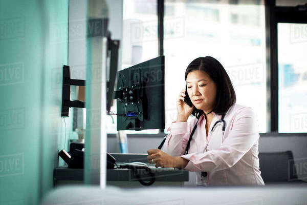 Female doctor using smart phone computer desk in clinic Royalty-free stock photo