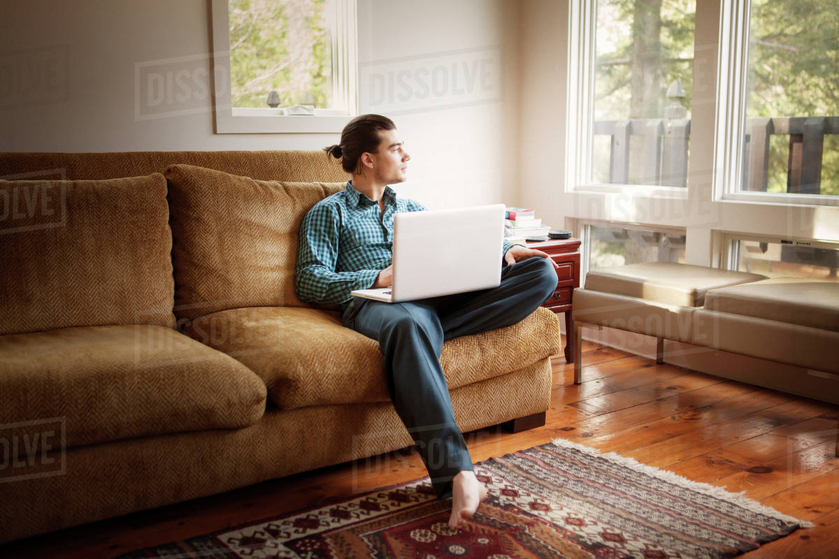 Man relaxing on sofa with laptop Royalty-free stock photo