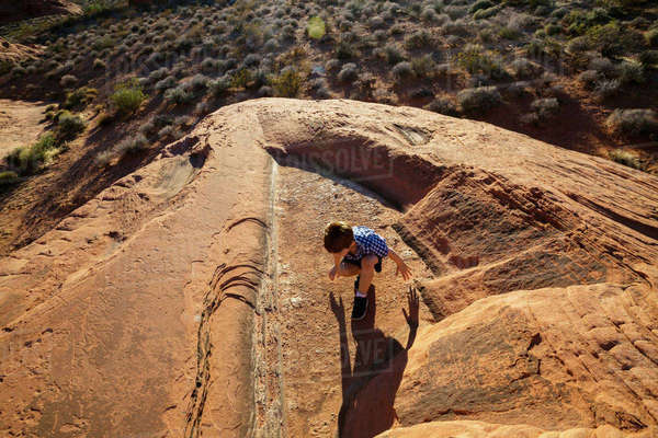 Overhead view of boy sitting on rock at Valley of Fire State Park Royalty-free stock photo