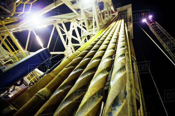 Low angle view of metallic machinery in oil rig against sky at night Royalty-free stock photo
