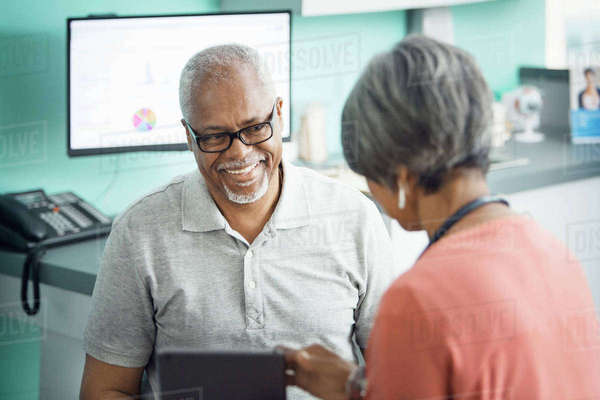 Happy senior male patient talking to female doctor in clinic Royalty-free stock photo