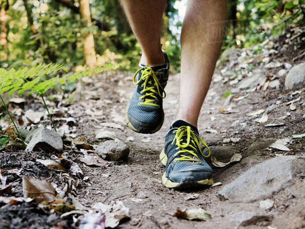 Low section of man walking on dirt footpath Royalty-free stock photo