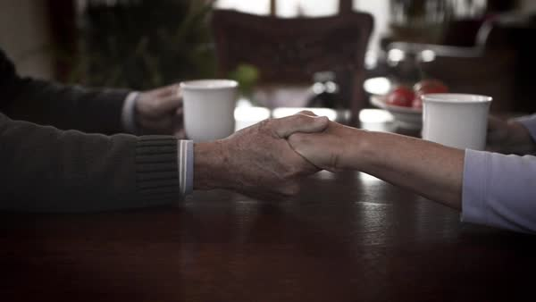 Slow motion of senior couple holding hands at dining table in house Royalty-free stock video