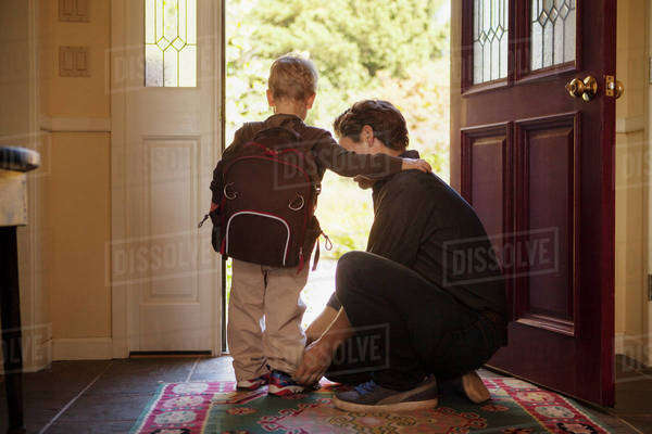 Dad helping son (2-3) put shoes on before school Royalty-free stock photo