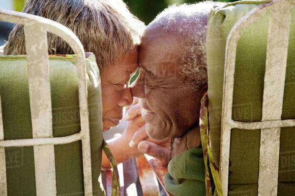 Senior couple eskimo kissing and holding hands sitting in armchairs Royalty-free stock photo