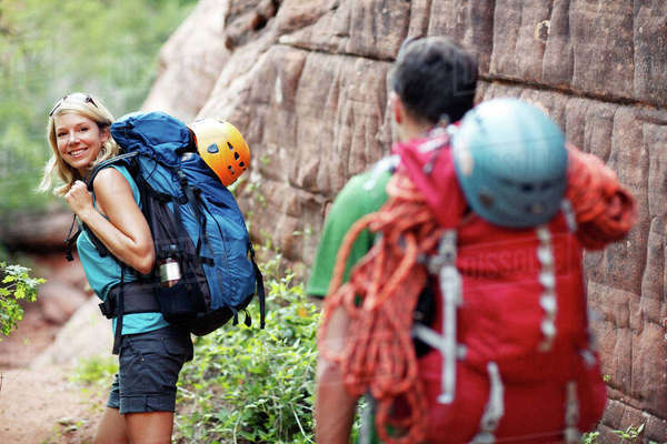 Rear view of couple walking with backpacks during hiking Royalty-free stock photo