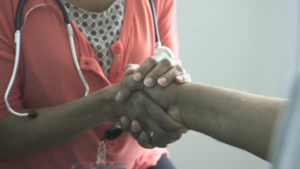 Lockdown shot of female doctor shaking hand with patient in clinic Royalty-free stock video