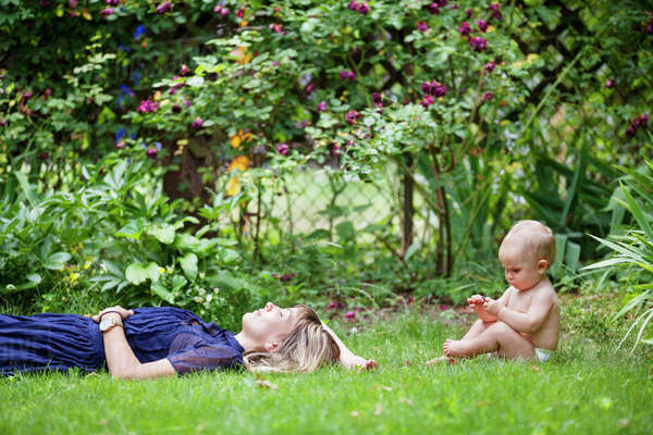 Mother sleeping by baby on grassy field at backyard Royalty-free stock photo