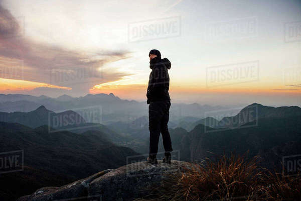 Man looking away while standing on mountain during sunset Royalty-free stock photo