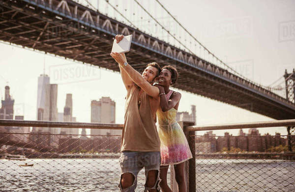 Multi-ethnic couple taking selfie through tablet computer against Manhattan Bridge and city skyline Royalty-free stock photo