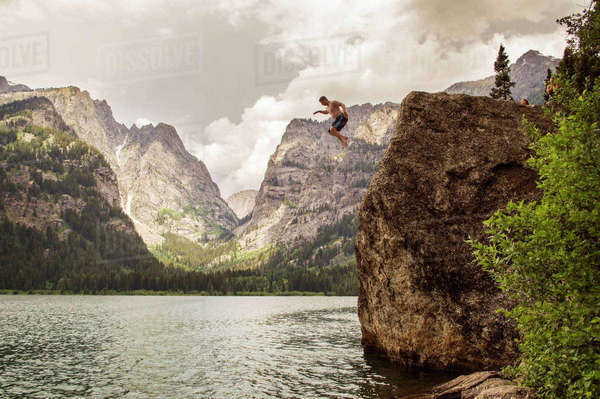 Man jumping from cliff into lake against mountains Royalty-free stock photo