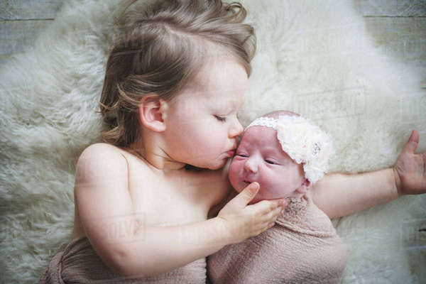 Girl kissing baby sister lying on rug at home Royalty-free stock photo