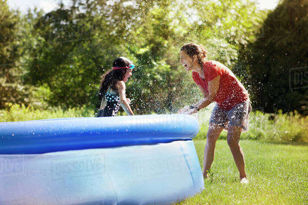 Mother and daughter (6-7) playing with hose in garden Royalty-free stock photo