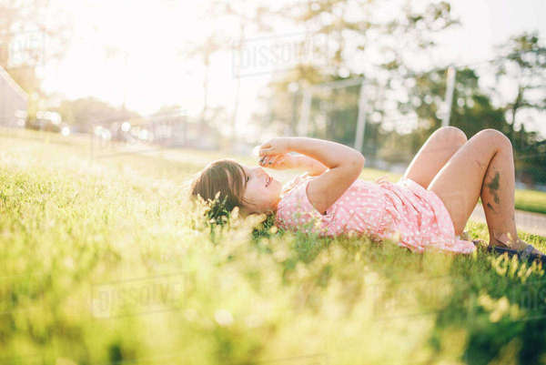 Messy girl lying on grassy field at park Royalty-free stock photo