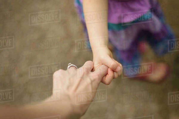 Cropped image of mother and daughter holding hands while walking on footpath Royalty-free stock photo
