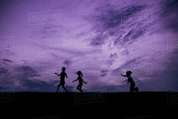 Happy sisters playing on field against dramatic sky during sunset Royalty-free stock photo