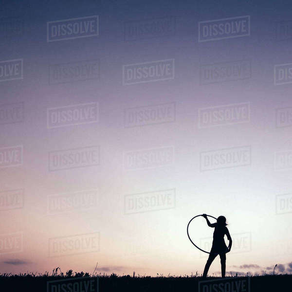 Silhouette girl playing with hula hoop against clear sky Royalty-free stock photo