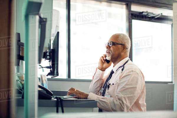 Doctor talking on mobile phone while using desktop computer in hospital Royalty-free stock photo