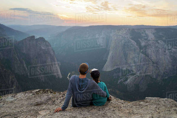 Rear view of couple sitting on mountain during sunset Royalty-free stock photo