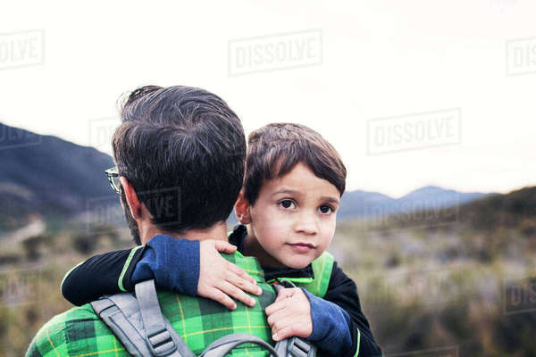 Father carrying son while walking on field against clear sky Royalty-free stock photo