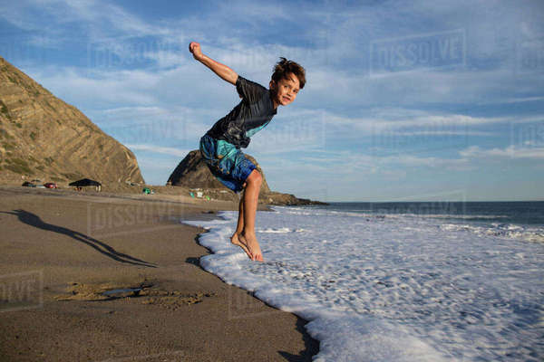 Portrait of boy jumping in surf at beach against sky Royalty-free stock photo