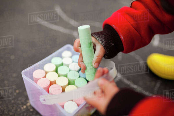 Cropped image of boy playing with chalks on street Royalty-free stock photo