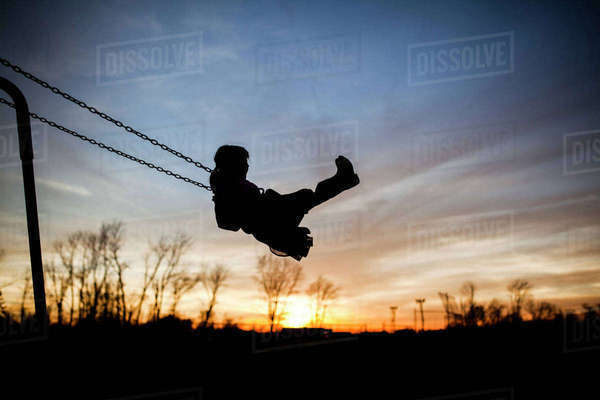 Silhouette girl playing on swing against sky during sunset Royalty-free stock photo