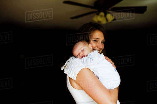 Portrait of smiling mother carrying baby girl at home Royalty-free stock photo