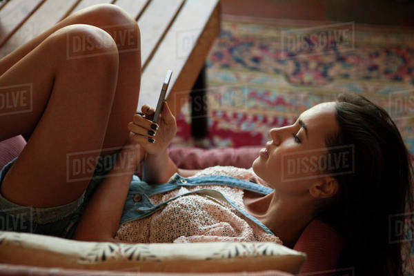 Young woman lying on armchair and using mobile phone Royalty-free stock photo