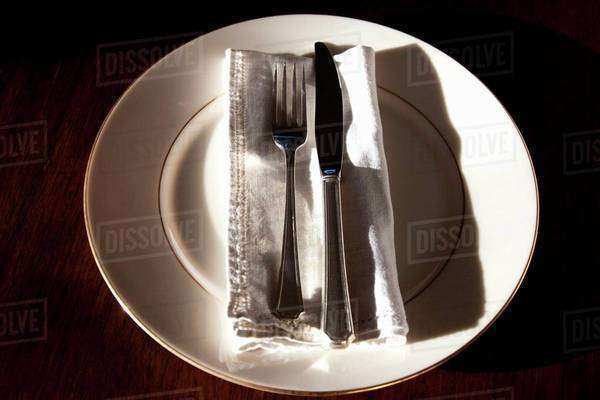 Silver Fork and Knife on Bone China Plate with Linen Napkin Royalty-free stock photo