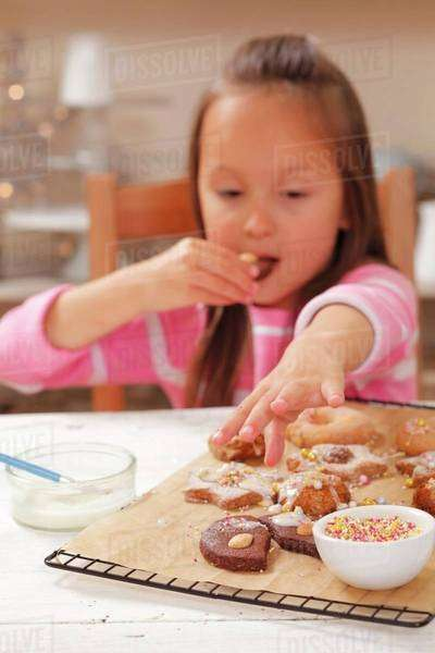 A girl eating freshly baked Christmas biscuits Royalty-free stock photo