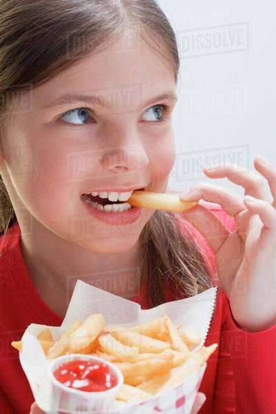 Girl holding a bag of chips and eating a chip Royalty-free stock photo